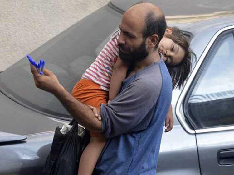 Padre refugiado y su hija vende lápices en la calle