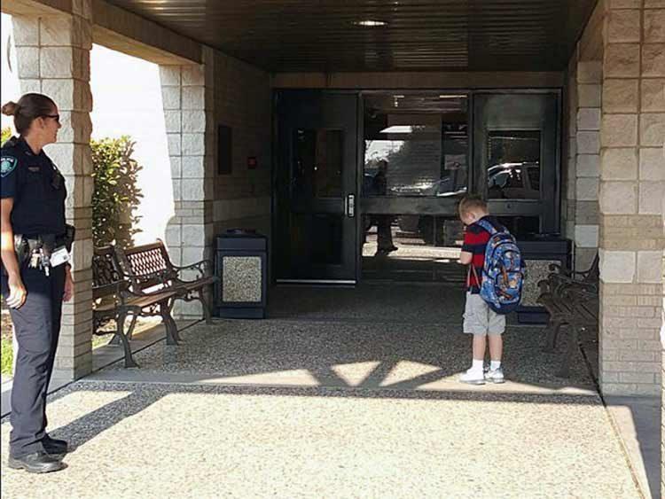 Niño que ora frente a la escuela es